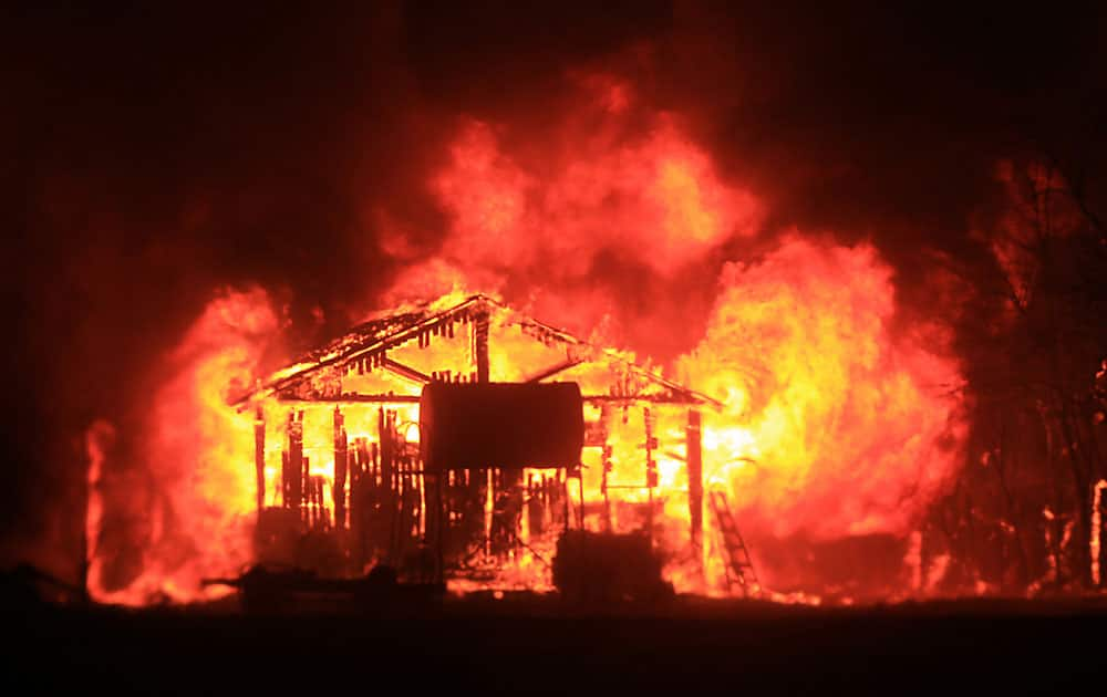 A home and shop are burned by the Valley fire as it enters Middletown,Calif., in Lake County.
