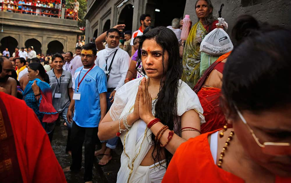 An Indian woman prays after taking a holy dip on the second