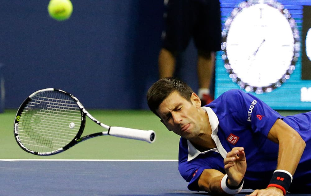 Novak Djokovic, of Serbia, falls to the court while trying to return a shot to Roger Federer, of Switzerland, during the men's championship match of the U.S. Open tennis tournament.