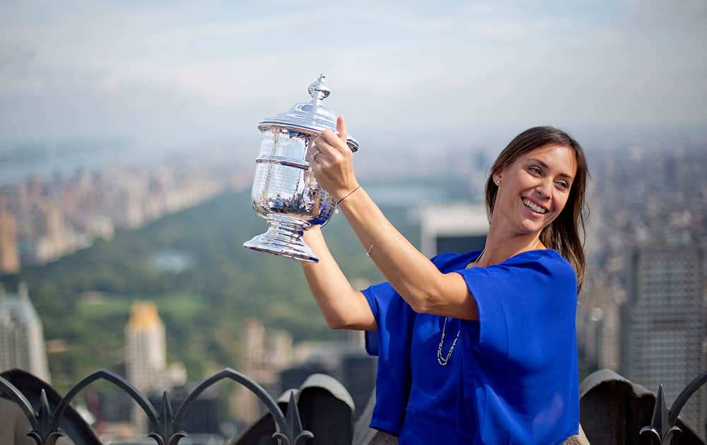 Flavia Pennetta, of Italy, holds the U.S. Open tennis women's singles championship trophy during a visit to the Top of the Rock Observation Deck at Rockefeller Center in New York.