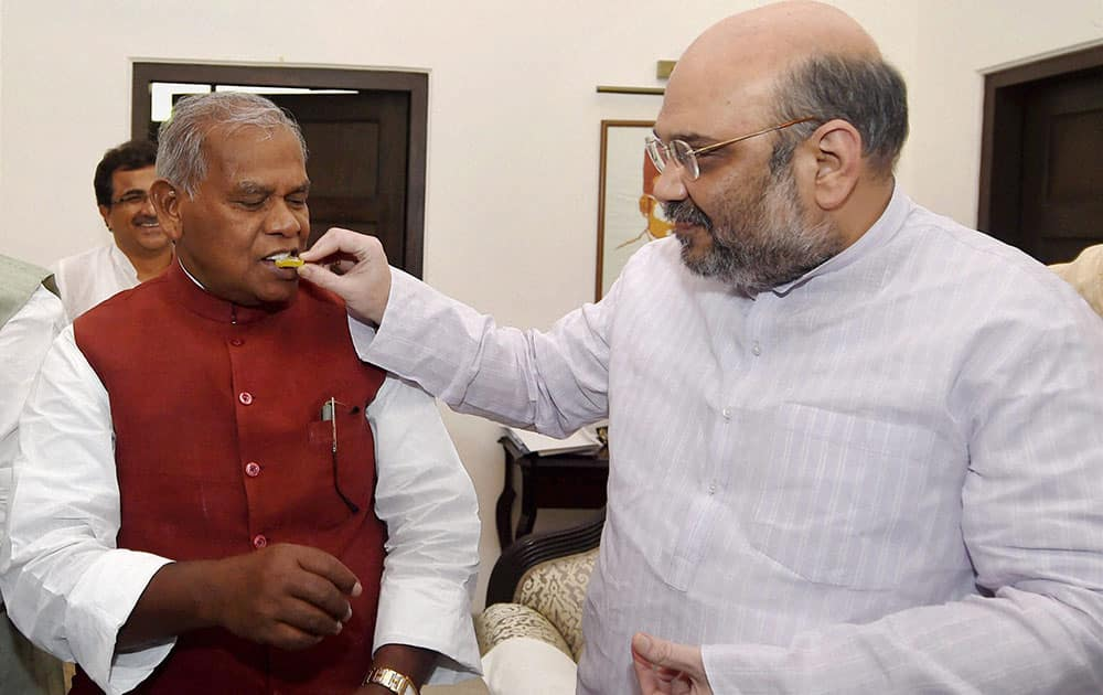 BJP President Amit Shah offers sweets to HAM(S) chief Jitan Ram Manjhi during a meeting regarding Bihar elections, in new Delhi.