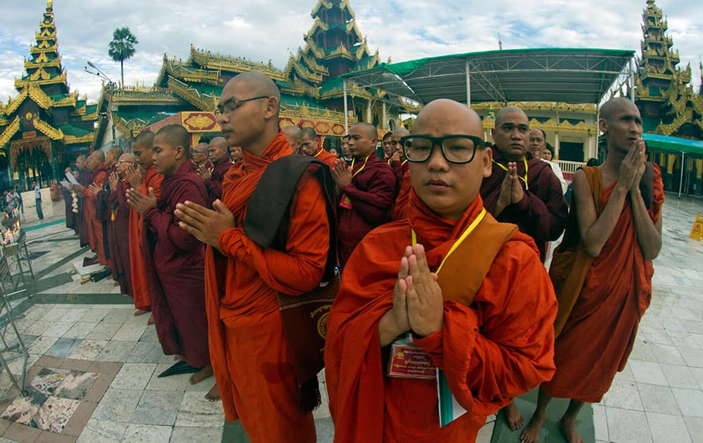 """Myanmar Buddhist monks pray at Shwedagon Pagoda before a ceremony to welcome the approval of """"Marriage Law"""", at parliament."""