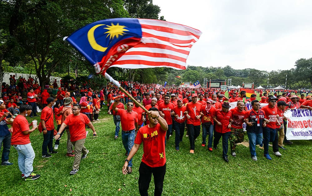 A pro-government 'red shirt' protestor waves the national flag during a rally in Kuala Lumpur, Malaysia.