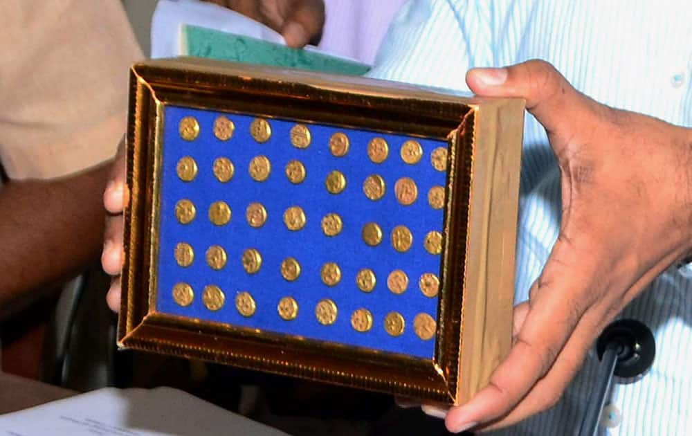 Officials of Department of Archaeology and Museums showing a treasure trove consisting of 40 ancient Gold Coins and a broken Brass container recovered from farm labouers by the police in Khammam district, in Hyderabad.