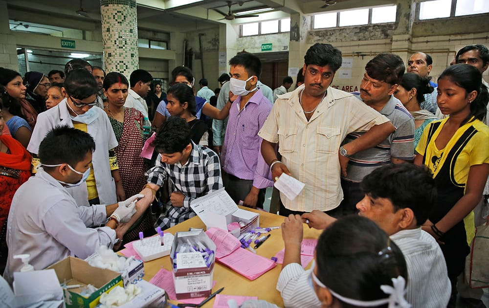 People suffering from fever get their blood test for dengue at a fever clinic run by a government hospital in New Delhi.