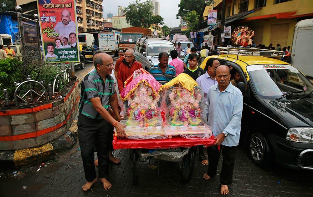 Devotees carry idols of elephant-headed Hindu god Ganesha on a handcart during Ganesha Chaturthi festival in Mumbai.