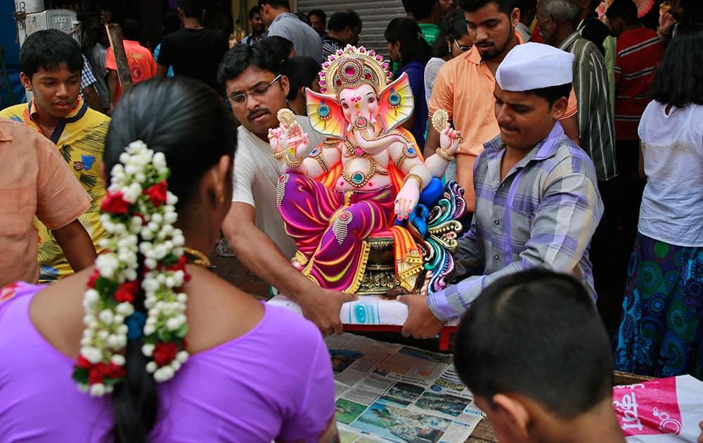 Devotees carry an idol of elephant-headed Hindu God Ganesha during Ganesh Chaturthi festival celebrations in Mumbai.