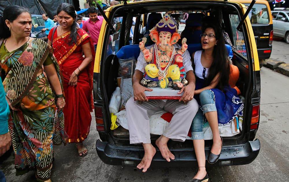 Devotees carry an idol of elephant-headed Hindu God Ganesha in the trunk of a taxi during Ganesh Chaturthi festival celebrations in Mumbai.