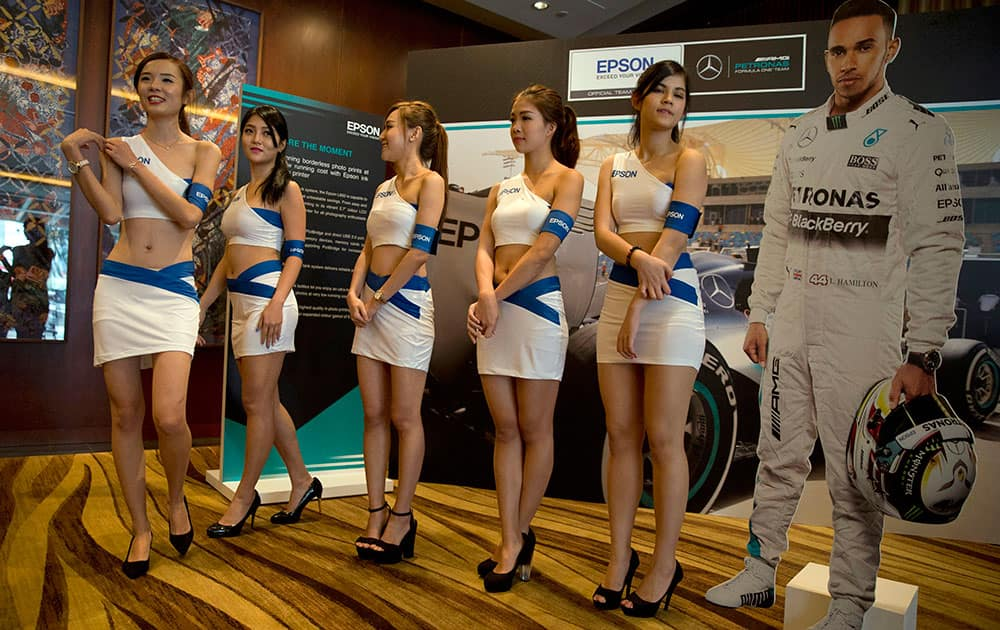 Ushers pose for photos near a cutout of Mercedes driver Lewis Hamilton of Britain during a promotional event ahead of the Singapore Formula One Grand Prix on the Marina Bay City Circuit in Singapore.