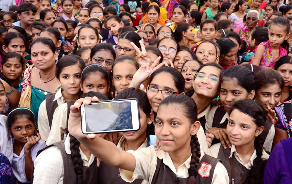 School girls in Ahmedabad take a selfie during a function to save and educate the girl child.