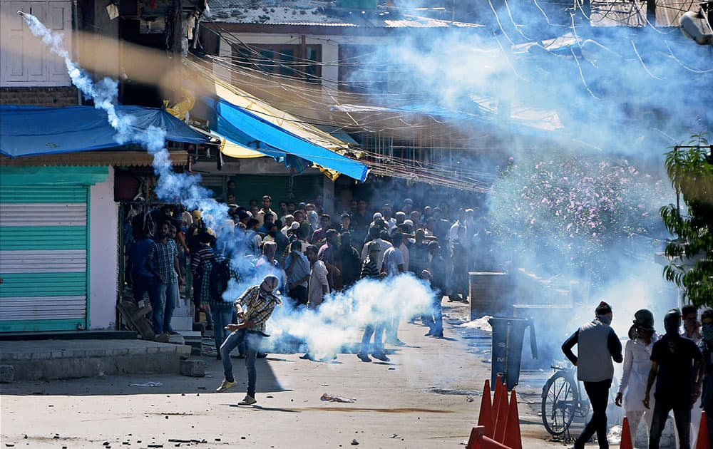 Youths throw stones and teargas shells back on police during clash between police and protesters who were protesting against the Beef ban by J&K High Court at Nowhatta in Srinagar.