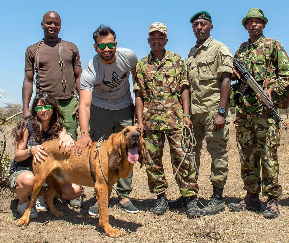 Rohit Sharma accompanied by his fiancee Ritika Sajdeh poses with an anti-poaching sniffer dog of Kenyan Police in Nairobi.