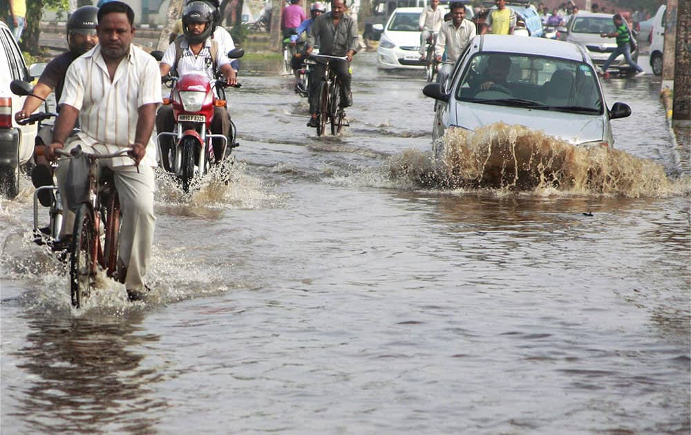 Vehicle moves through a water logged after heavy rains in Gurgaon.