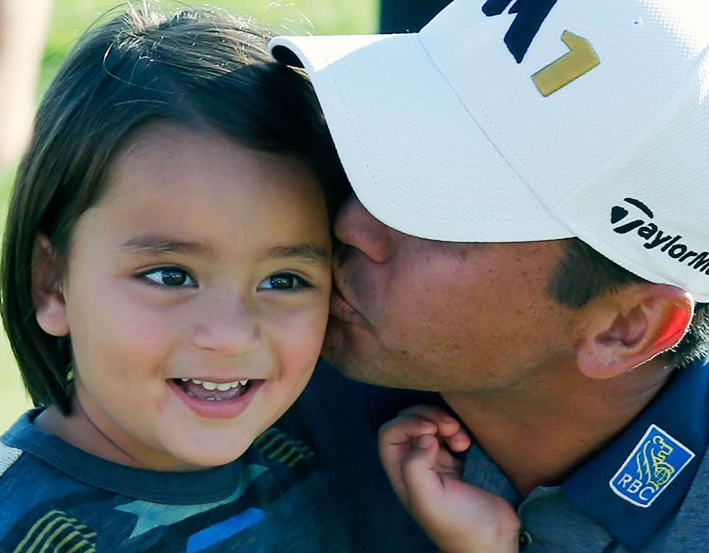 Jason Day of Australia, kisses his son Dash, after winning the BMW Championship golf tournament at Conway Farms Golf Club in Lake Forest, Ill.