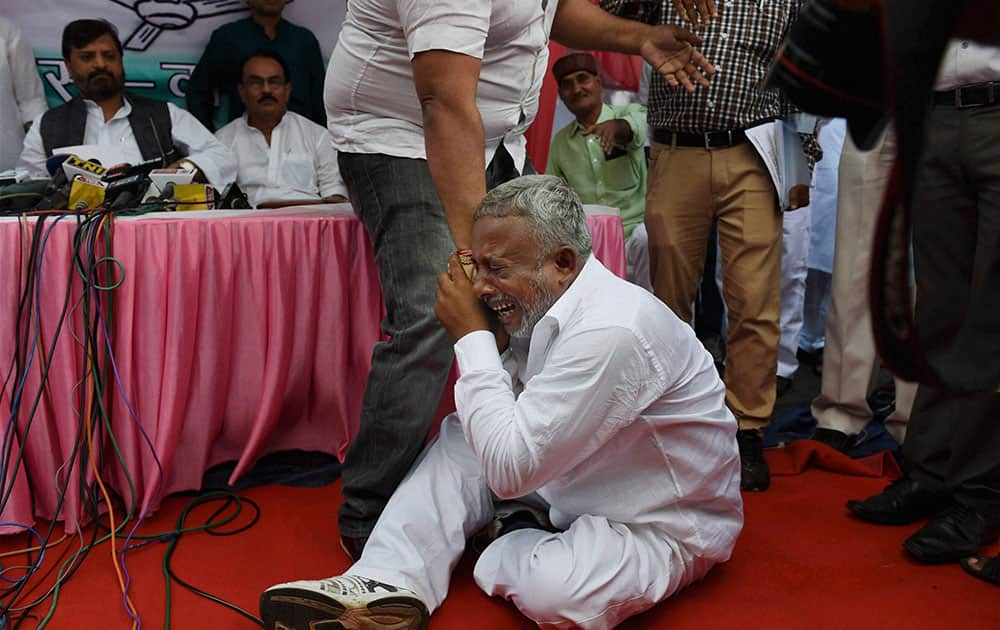 A ticket aspirant, Ashok Gupta is taken away after he tried to disrupt a press conference of RLSP chief Upendra Kushwaha in New Delhi.