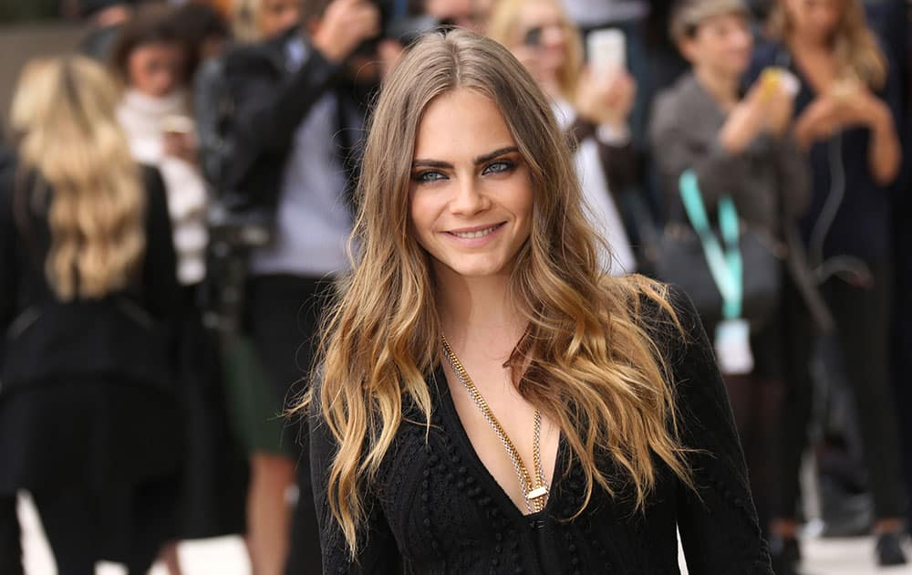 British model Cara Delevingne poses for photographs as she arrives for the Burberry Prorsum Womenswear Spring and Summer show in London.