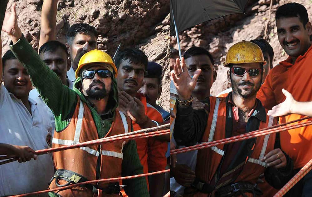 Satish Tomar (R) and Mani Ram, the two tunnel workers who were trapped for nine days inside an under-construction tunnel, wave at the crowd after being brought out by the NDRF team in Bilaspur.