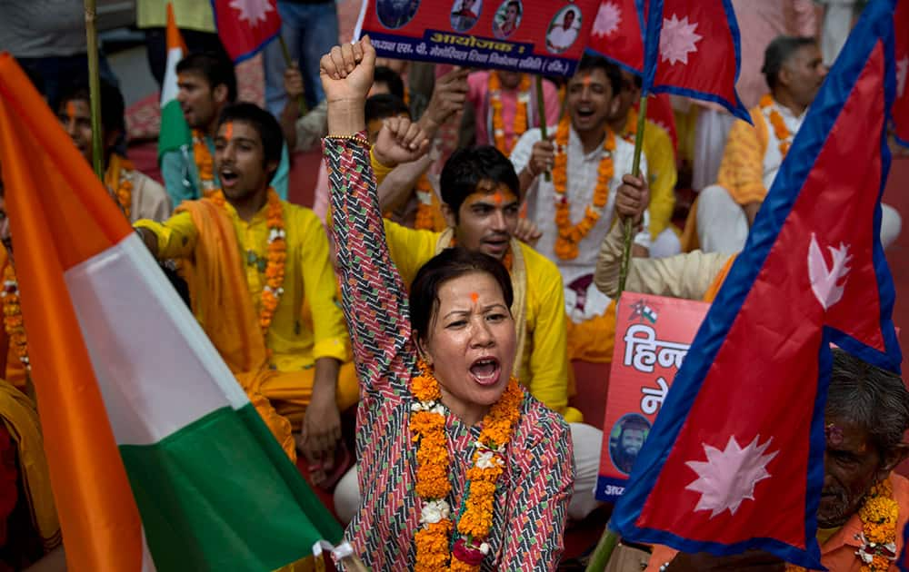 A Nepali woman shouts slogans during a protest against the Nepalese government and demanding it be restored as a Hindu nation, in New Delhi.