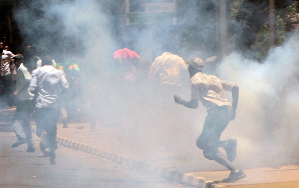 A university student run as police use tear gas to disperse students during demonstration in Nairobi, Kenya.