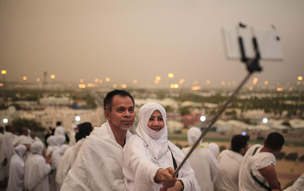 A Muslim pilgrim couple take a selfie on a rocky hill called the Mountain of Mercy, on the Plain of Arafat, near the holy city of Mecca, Saudi Arabia.