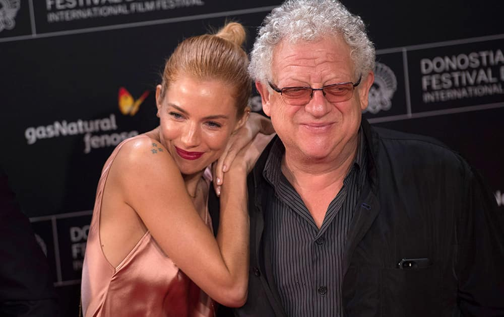 British actress Sienna Miller, poses for photographers beside film director, Jeremy Thomas, on arrival at the Kurssal cinema to promote the film, ''High Rise'', during the 63rd San Sebastian Film Festival.