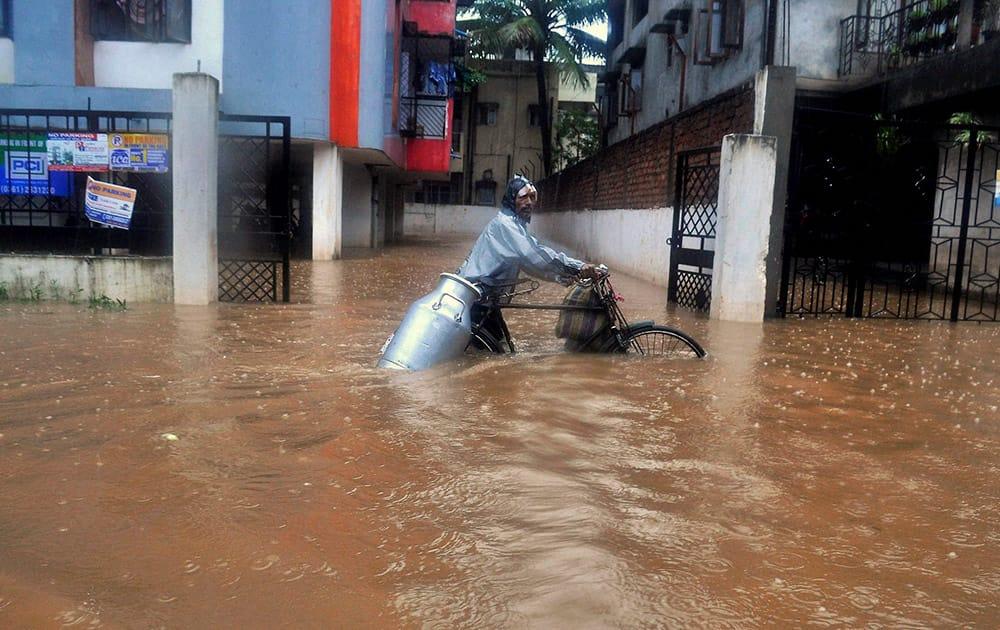 A milk vendor wades through a waterlogged street at Anil Nagar in Guwahati.