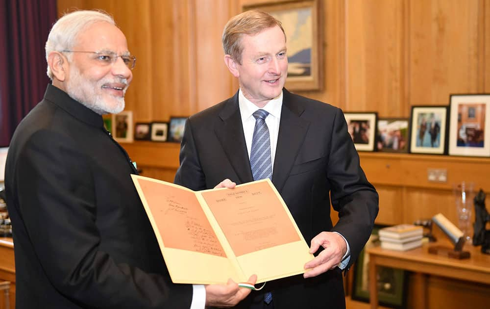 Prime Minister Narendra Modi presenting a document to his Irish counterpart Enda Kenny at a meeting in Dublin.