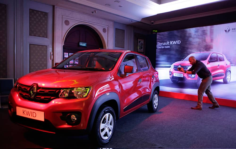 A man takes a photograph of a Renault Kwid car during its launch in New Delhi. The price starts at Indian Rupees 256,968 (US$ 3888).