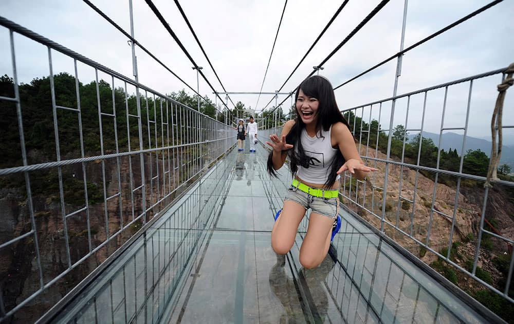 A woman plays around as she walks across a glass-bottomed suspension bridge in a scenic zone in Pingjiang county in southern China's Hunan province. The bridge, 300 meters (984 feet) long and 180 meters (590 feet), opened to visitors on Thursday for the first time since its conversion from a regular suspension bridge was completed.