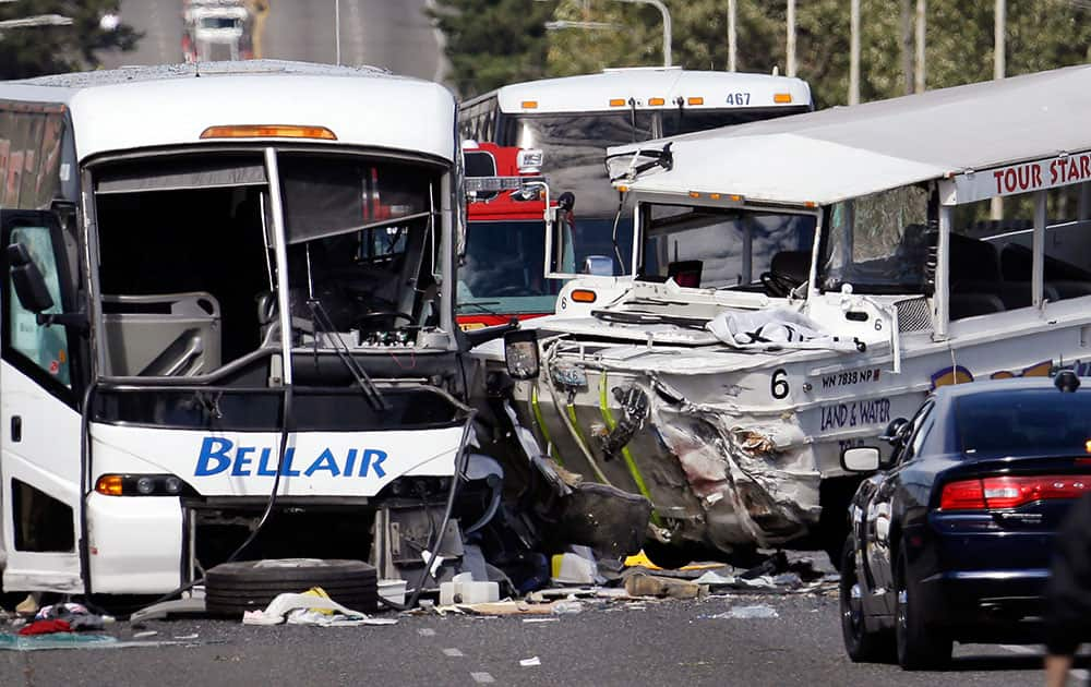 A charter bus, left, and an amphibious tour vehicle remain on the Aurora Bridge after colliding in a deadly crash involving several vehicles in Seattle.