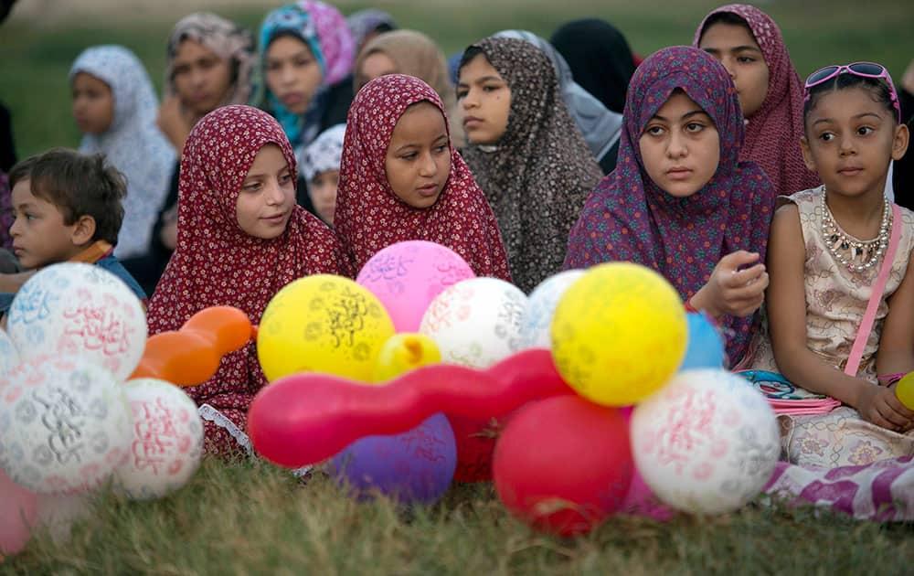 Palestinian girls wearing hijabs take part in the Eid al-Adha prayer in a public garden in Gaza City.