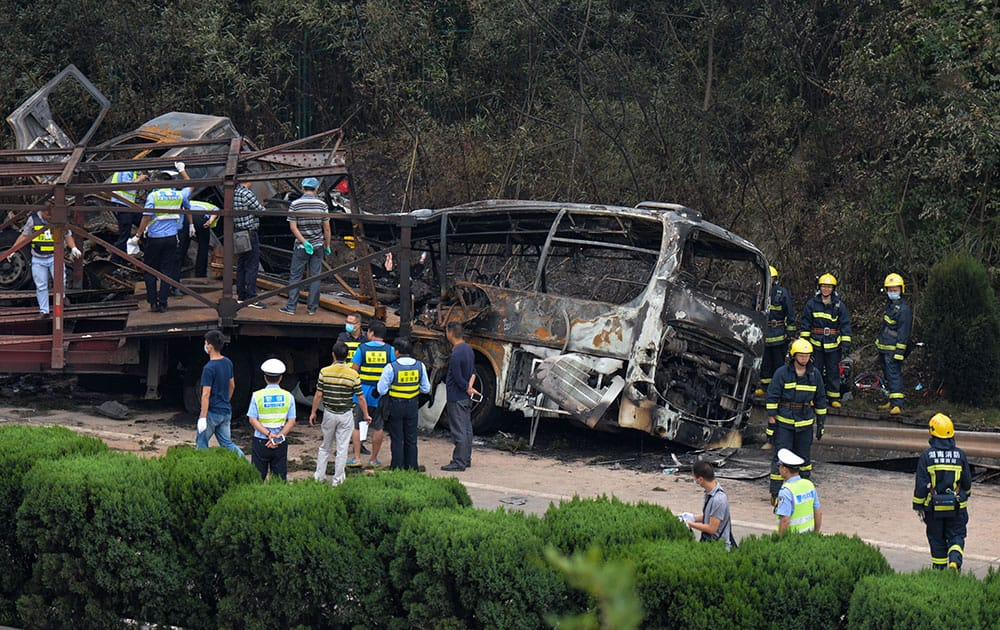 In this photo provided by China's Xinhua News Agency, rescuers work at the site of a highway accident in central China's Hunan Province. The government in Hunan province said in a statement that a flatbed truck lost control and veered into opposite lanes of traffic while dragging a smaller truck driving in the same direction. The trucks collided with an oncoming coach bus and a van, causing a fire, the statement said.