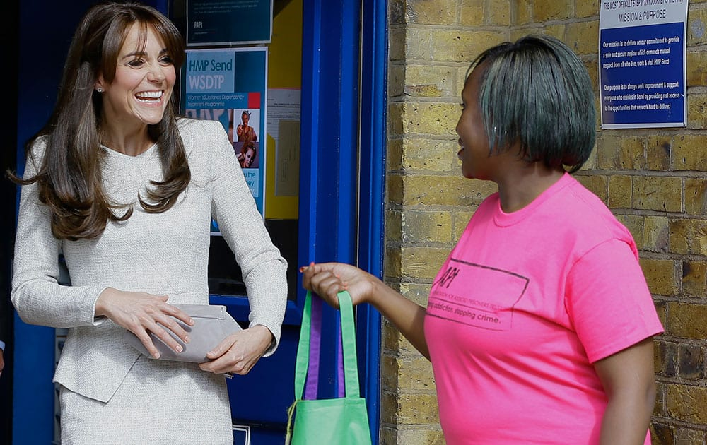 Britain's Kate, Duchess of Cambridge smiles as she is handed a gift by Isha Walker who is on the RAPT programme, during a visit to Her Majesty's Prison Send near Woking, England.