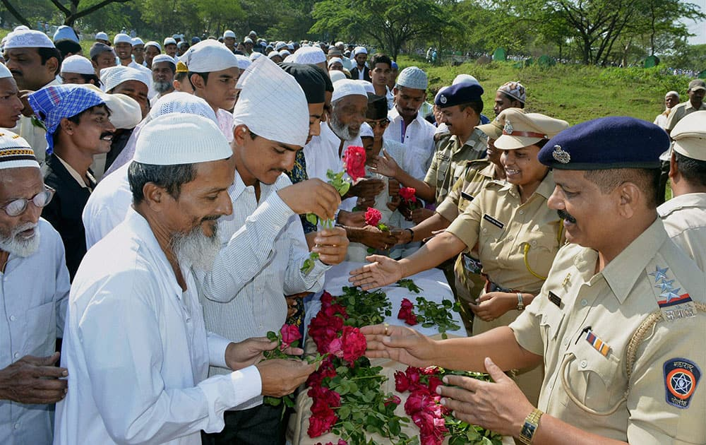 Police officers giving roses to Muslims while greeting them on the occasion of Eid-al-Adha in Karad.