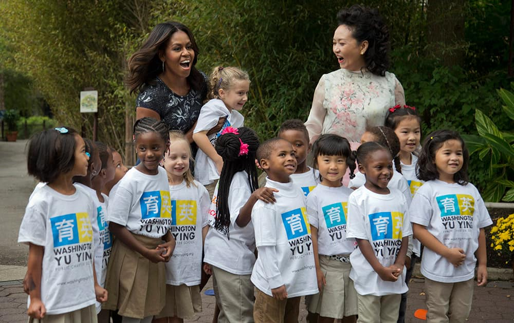 First lady Michelle Obama and China's first lady Peng Liyuan, are greeted by third graders from Yu Ying Public Charter School in Washington, during a visit to the Smithsonian's National Zoo in Washington.