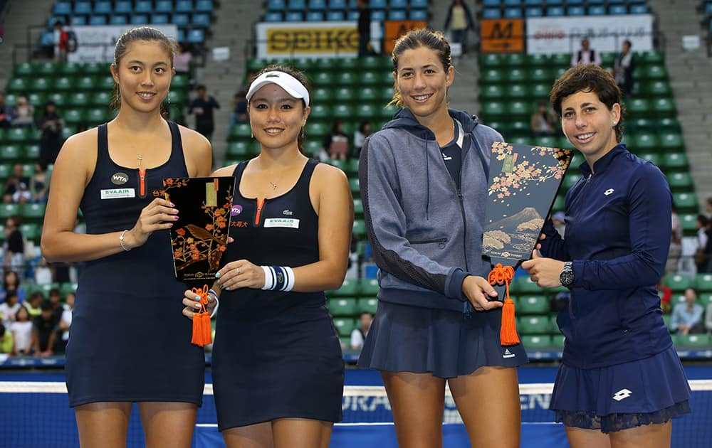 Spain's Garbine Muguruza, and Carla Suarez Navarro, right, hold their doubles trophy, along with runners-up Taiwan's Chan Yung-jan, second left, and Chan Hao-ching, during the award ceremony at the Pan Pacific Open women's tennis tournament in Tokyo.