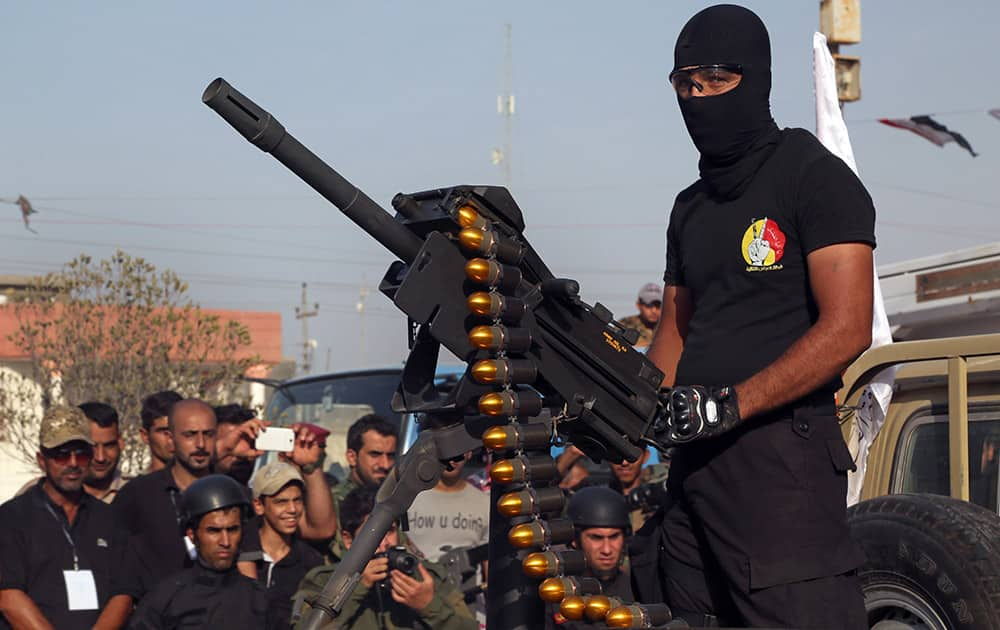 A members of the Abbas combat squad, a Shiite militia group, wearing a shirt with the group's logo, mans a gun atop a vehicle during a military parade in Basra, 340 miles (550 kilometers) southeast of Baghdad, Iraq.