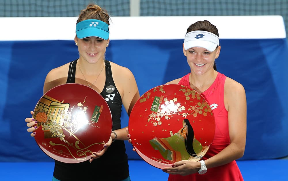 Agnieszka Radwanska of Poland, right, holds the championship trophy along with runner-up Belinda Bencic of Switzerland, left, after defeating Bencic in their women's singles final at the Pan Pacific Open women's tennis tournament in Tokyo.