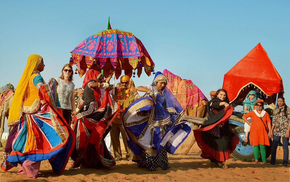 Foreign tourists dance with local artists on the occasion of World Tourism Day in Pushkar.