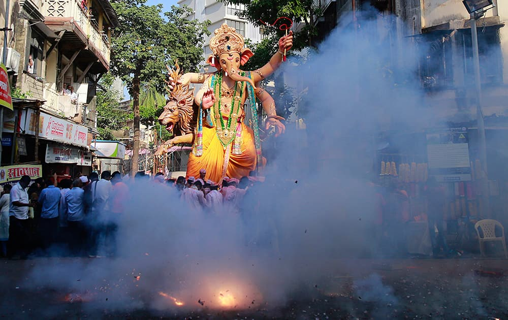 People light firecrackers as an idol of elephant-headed Hindu god Ganesha is taken through the streets prior to its immersion in the Arabian Sea in Mumbai.