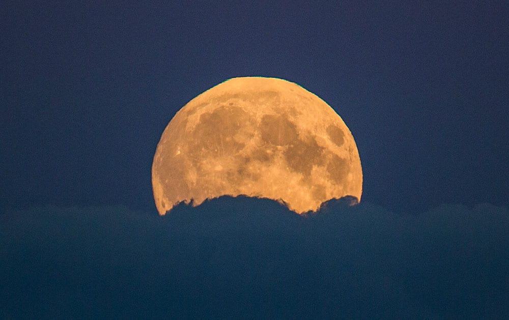 A full moon rises between clouds in Berlin, Germany.