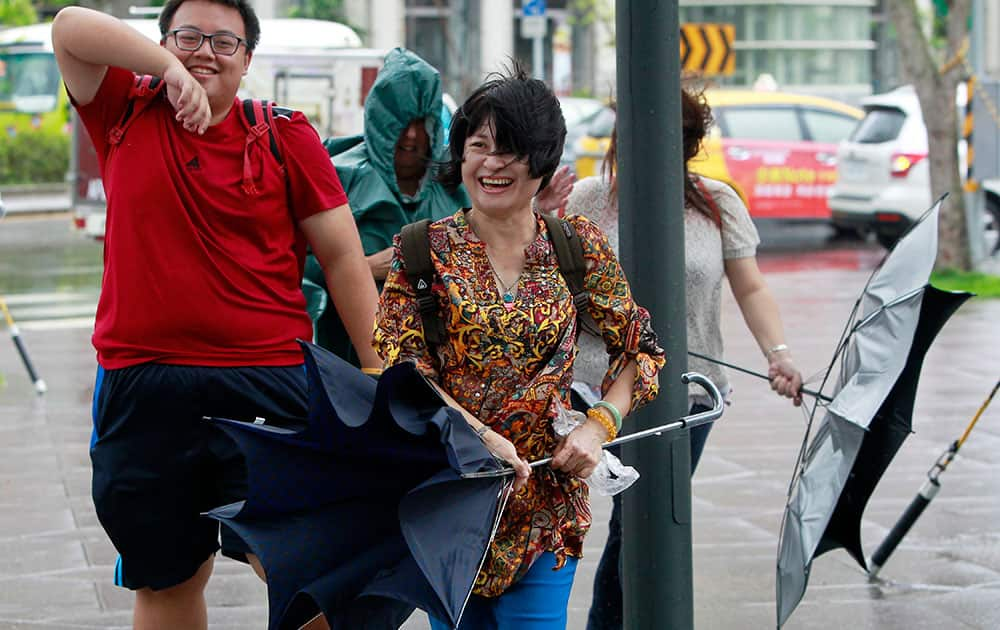 People struggle with winds from approaching Typhoon Dujuan in the business district of Taipei, Taiwan.