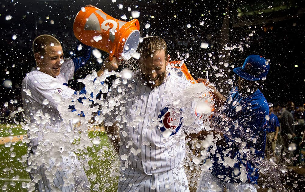 Chicago Cubs Chris Denorfia has water dumped on him by teammates Anthony Rizzo, left, and Dexter Fowler, right, after a walk-off home run against the Kansas City Royals during the 11th inning of a baseball game in Chicago.