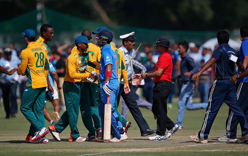 A policeman tries to secure the players after spectators invaded the pitch at the end of a practice Twenty20 match between South Africa and India A team in New Delhi.