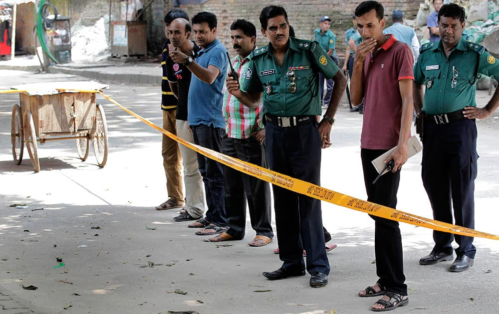 Members of Bangladeshi police and detective branch stand by the site where Italian citizen Cesare Tavella was gunned down by unidentified assailants in Dhaka, Bangladesh.