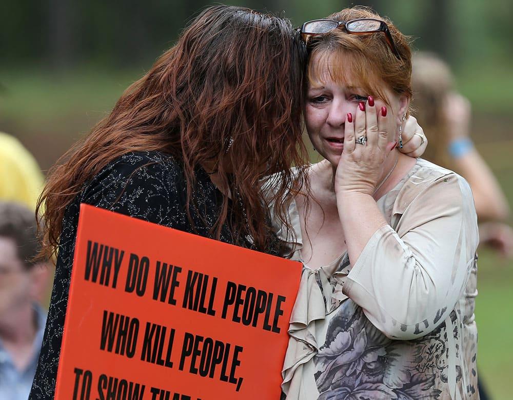 Dawn Skorcik, left, of Marietta, Ga., and Dawn Barber, of Powder Springs, Ga., comfort each other while protesting outside of Georgia Diagnostic Prison in Jackson, Ga.