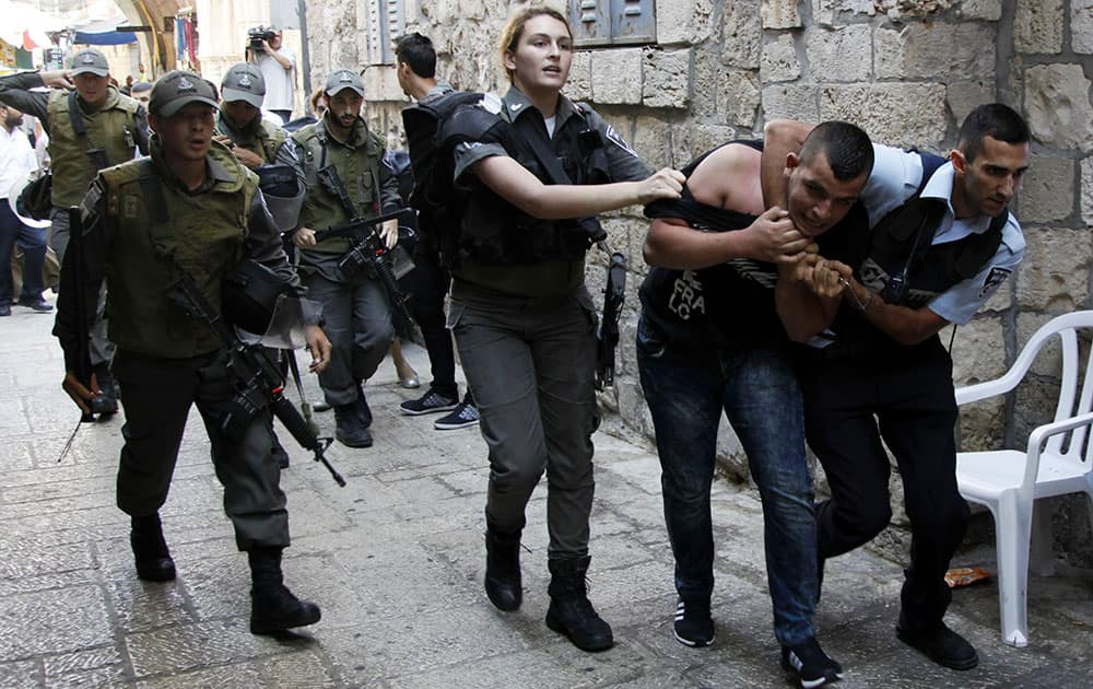 Israeli policemen arrest a Palestinian man during confrontations in the Old City in Jerusalem.