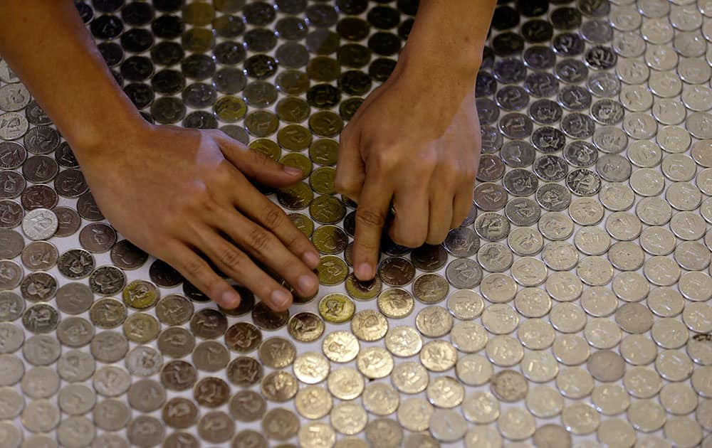 An employee of an international money remittance company arranges coins in an attempt to set a new Guinness world record for the largest coin mosaic at suburban Quezon city northeast of Manila, Philippines.