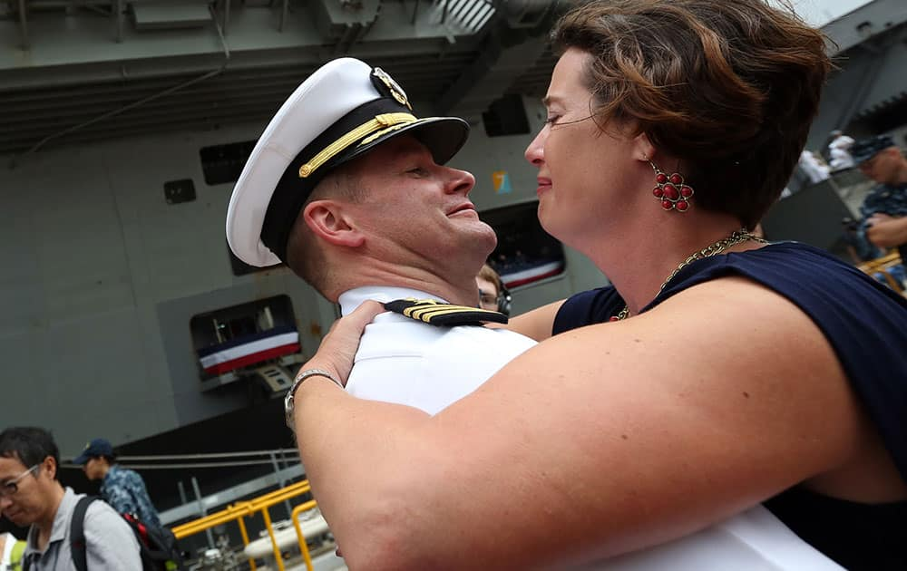 A crew member of U.S. navy nuclear-powered aircraft carrier USS Ronald Reagan reunites his loved ones upon arrival at the U.S. Navy's Yokosuka base in Yokosuka, south of Tokyo.