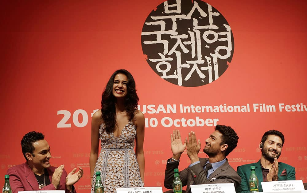 Indian actress Sarah Jane Dias, second from left, is congratulated by Indian director Mozez Singh, left, actor Vicky Kaushal and actor Raaghav Chanana , right, after she sings a song during a press conference for the Busan International Film Festival opening movie
